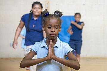aim to empower yoga class child